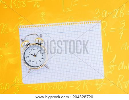 back to school concept - alarm clock on ruled paper on yellow background with math formulas