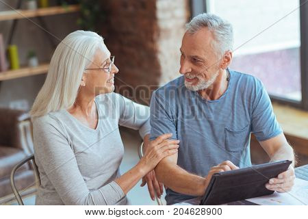 Reliable relationships. Pleasant aged loving couple resting at home and talking while feeling happy