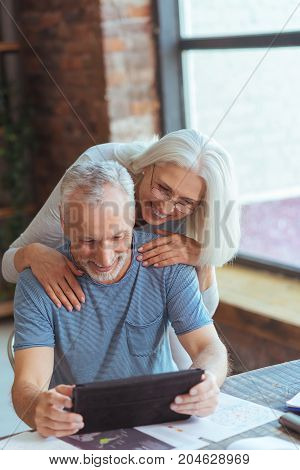 Pleasant time at home. Pleasant aged man sitting at the table and using tablet while his wife standing behind him