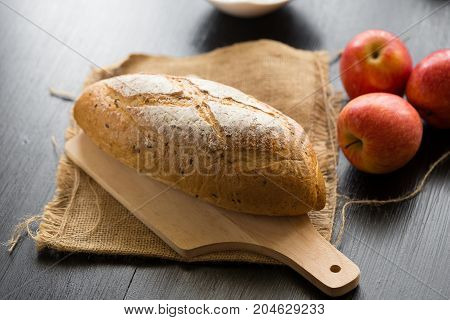 French Bread Baguette Cut On Wooden Board With Knife.  With Red Apple