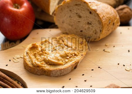 French Bread Baguette Cut On Wooden Board With Knife. With A Peanut Butter And Red Apple.