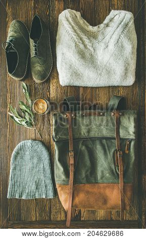 Flat-lay of Fall lady' s clothes outfit. Ecru colored knitted woolen sweater with braids, haki suede leather boots, large green backpack, grey cap and cup of coffee over wooden background, top view