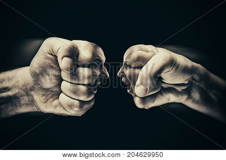 Two fists with a male and female face collide with each other on black background. Concept of confrontation competition family quarrel etc.