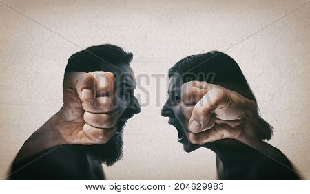 Double exposure image. A man and a woman scream at each other their silhouettes are combined with a picture of fists to enhance drama.