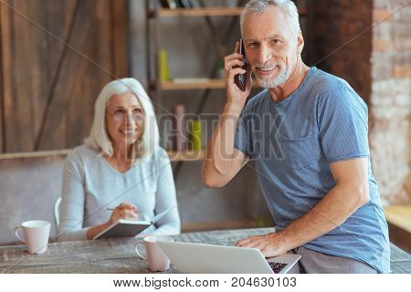 Work at home. Positive retired man using his laptop and talking on smart phone while his wife making notes in the background