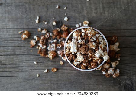 chocolate popcorn in a red dish on wooden background