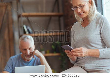 write me back. Cheerful beautiful aged woman using her smart phone and texting while her husband using the laptop in the background