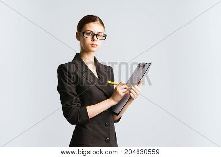A strict professor in glasses with a tablet for paper in the hands and glasses looks into the camera skeptical