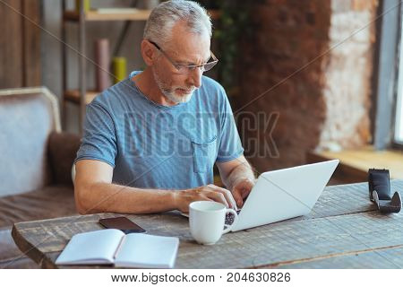 Involved in work. Pleasant handsome retired man sitting at the table and typing while working in house