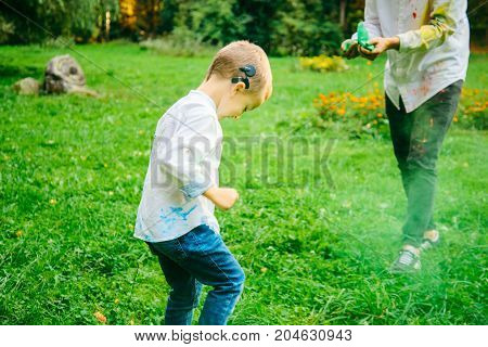 Boy with hearing aid playing with holi paints in city park