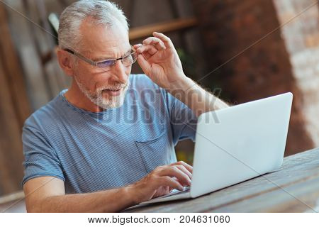 Surf the Internet. Waist up of a cheerful aged man sitting at the table and using his laptop while touching his glasses