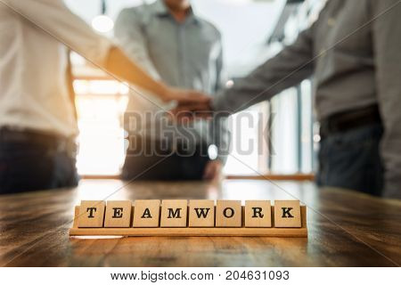 Teamwork word on wood table with Business team work join hands together concept in background