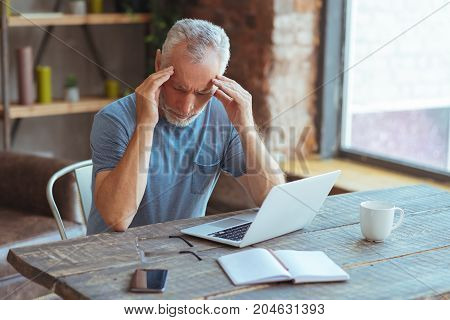 Terrible ache. Sick elderly man sitting at the table and having a headache while feeling cheerless