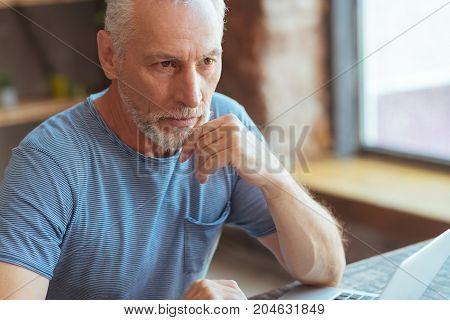 Let me think. Serious thoughful aged man sitting at the table and using laptop while mulling over his problems