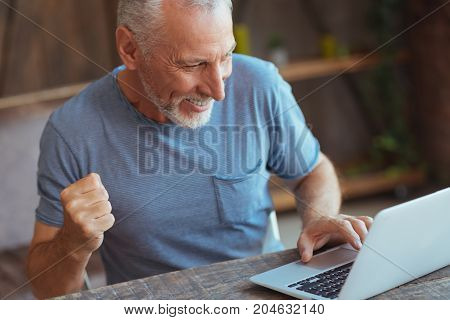Happy victory. Overjpyed aged smilign man sitting at the table and showing jubilation while using his laptop