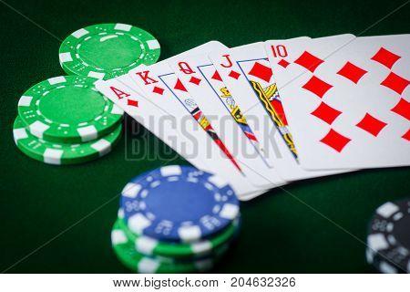 Royal flash and poker chips on green casino table. gambling success.