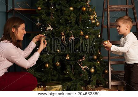 Happy smiling mother and little son decorating Christmas tree together. Loving parent and child having fun at home. Merry Christmas and Happy holidays.