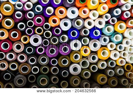 Multicolored thread coils from above, background flatly