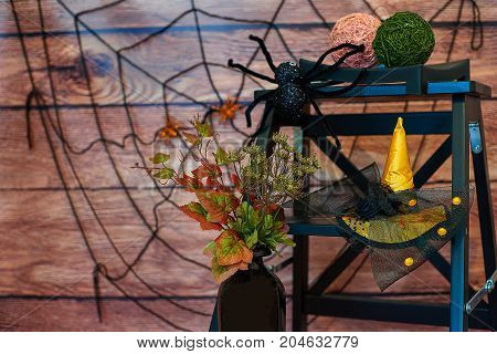 Halloween still-life with vase, plant, spider and hat