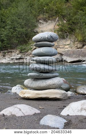 Pyramid of stones on the banks of the river. Stones pyramid on sand symbolizing zen, harmony, balance.