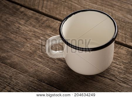 Old enamel empty cup on a wooden surface.