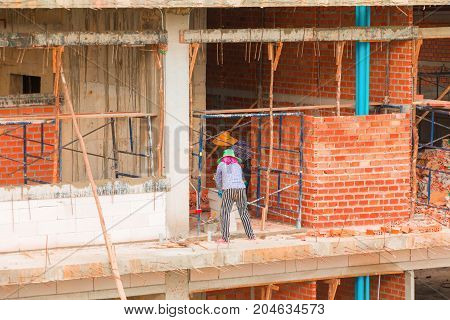 Bricklayer Female worker work industrial installing wall bricks in construction site