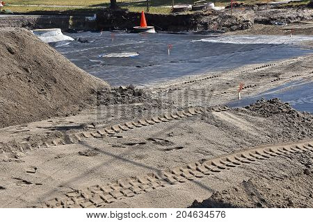 A street repair and road building construction site exposing a plastic vapor barrier, storm sewer pipers  and sand to be spread over the area.