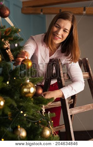 Young caucasian woman decorating Christmas tree with golden toys at home. Merry Christmas and Happy Holidays.