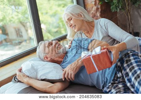 Sweet morning. Cheerful aged man lying in bed while his loving beautiful wife presenting a birthday present to him