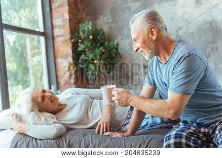 Pleasant morning. Cheeful aged smiling man bringing a cup of tea for his wife who is lying in bed and expressing love