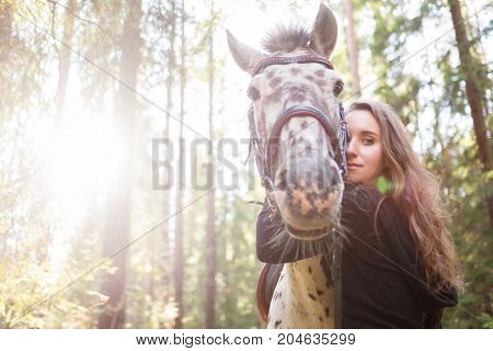 Young caucasian woman taking care of her horse, hugging his neck. Horse is white in brown spot. They arre walking in forest. Film effect