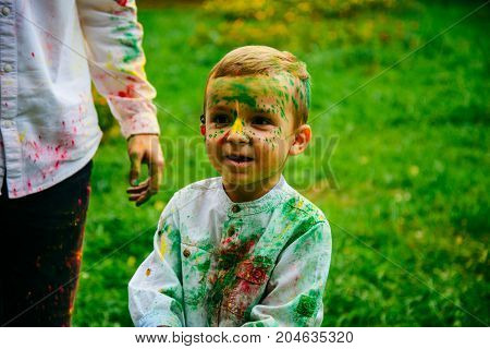 Fathers and children in the park palys with holi paints in summer day