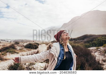Young woman on vacations enjoying happy moments. Attractive female enjoying a winter day on the beach with her arms outstretched and eyes closed.