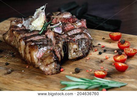 Sliced grilled T-bone steak tomatoes on dark background