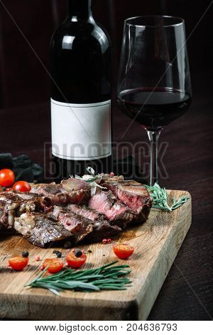 Sliced grilled T-bone steak tomatoes with bottle of wine and wineglass on dark background