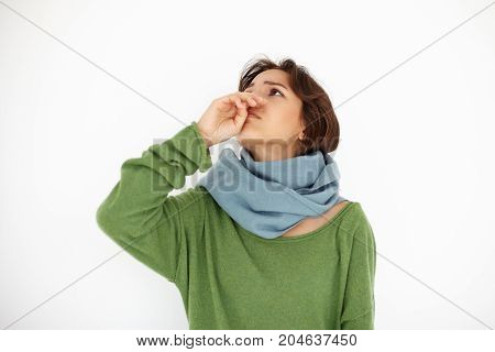 Horizontal shot of worried unhappy young woman wrapped in scarf throwing head back having running nose while suffering from cold or flu. Sickness disease unwellness allergy and healthcare concept