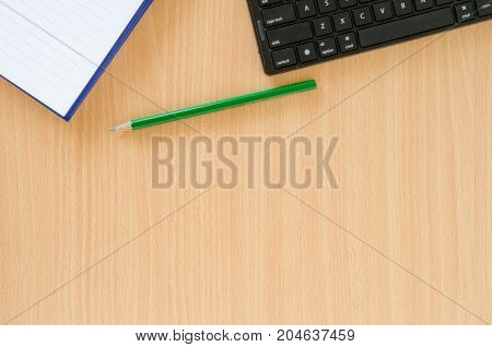 Note book and green pencil and black keyboard put on beech color background table with copy space.