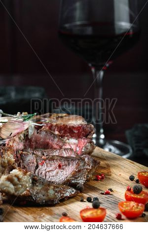 Sliced grilled T-bone steak tomatoes and on a cutting board with wineglass on dark background