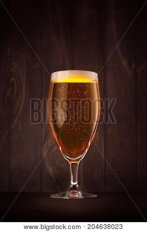 Goblet beer glass with golden sparkling lager on dark wood board vertical. Template for advertising design branding identity restaurant menu cover.