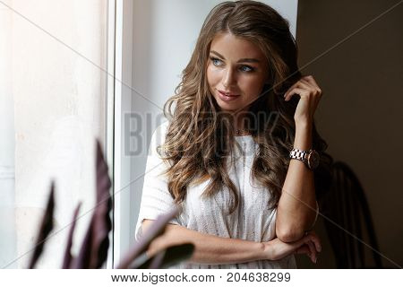 Picture of romantic gorgeous young woman of European appearance dressed in white blouse standing by window and looking through glass outside with dreamy thoughtful smile touching her voluminous hair