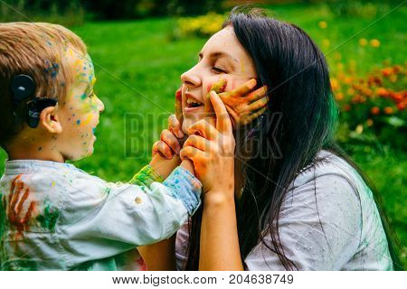 Happy mother and son playing with holi paints in city park