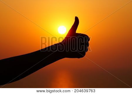 Thumb up gesture. Silhouette of the thumb up sign on the sunset
