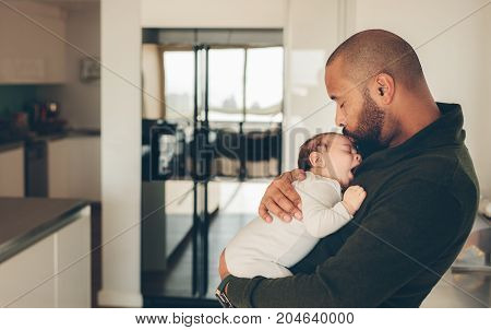 Man carrying his newborn son and kissing on his forehead. Cute little boy in his father's arms.
