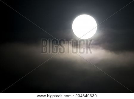 The moon in the haze of the clouds at night .