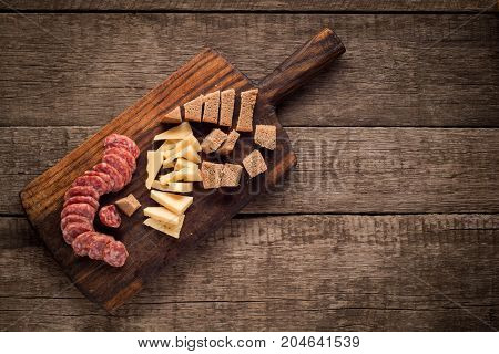 Cutting board with Salami, cheese and bread on dark wooden background.