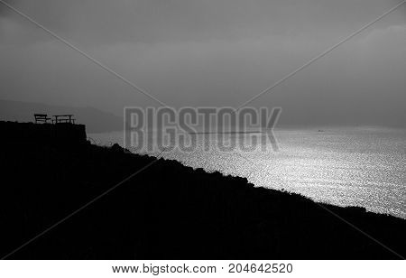A black and white Silhouette of a lonely bench on a cliff top overlooking the sea