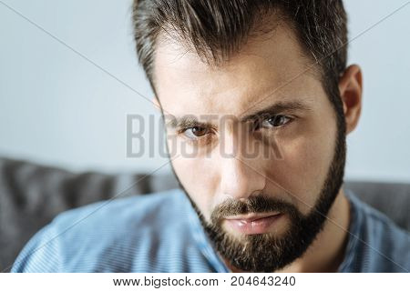 Sad eyes. Portrait of a cheerless gloomy handsome man looking at you while feeling unhappy