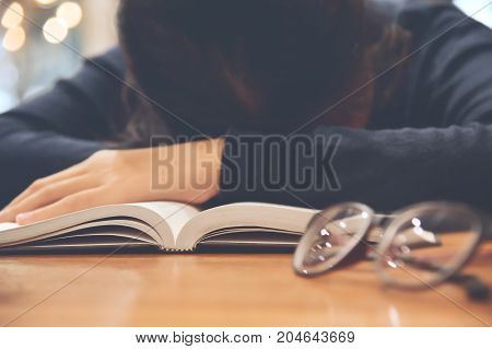 Focus on the book. Tired Asian woman sleeping with her book on wooden table.