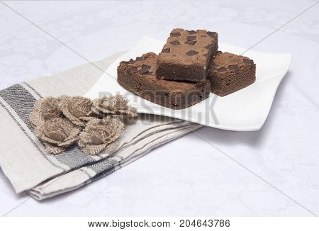 Chocolate brownie slices on a white plate with hessian flowers
