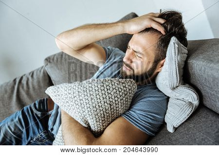 Health problems. Depressed nice young man lying on the sofa and holding his forehead while suffering from a headache